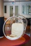 Ημικυκλική κρεμώντας καρέκλα πέρα από το κόκκινο χαλί στο δωμάτιο υποδοχής Στοκ Εικόνα