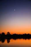 Ημισεληνοειδές φεγγάρι πέρα από το ηλιοβασίλεμα Στοκ Φωτογραφία