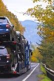 Ημι φορτηγό μεταφορέων αυτοκινήτων που μεταφέρει τα αυτοκίνητα στο θεαματικό φθινόπωρο γεια Στοκ φωτογραφία με δικαίωμα ελεύθερης χρήσης