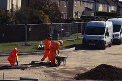Ηνωμένο Βασίλειο, Corby 25 Σεπτεμβρίου 2018 - εργαζόμενοι εικόνας fiew στα πορτοκαλιά ειδικά κοστούμια, σε μια οδοποιία στοκ εικόνες