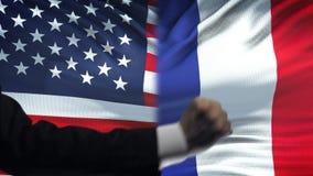 ΗΠΑ εναντίον της αντιμετώπισης της Γαλλίας, διαφωνία χωρών, πυγμές στο υπόβαθρο σημαιών φιλμ μικρού μήκους