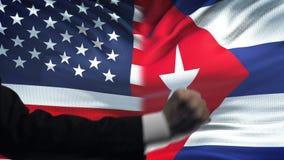 ΗΠΑ εναντίον της αντιμετώπισης της Κούβας, διαφωνία χωρών, πυγμές στο υπόβαθρο σημαιών απόθεμα βίντεο