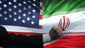 ΗΠΑ εναντίον της αντιμετώπισης του Ιράν, διαφωνία χωρών, πυγμές στο υπόβαθρο σημαιών απόθεμα βίντεο