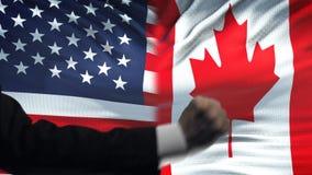 ΗΠΑ εναντίον της αντιμετώπισης του Καναδά, διαφωνία χωρών, πυγμές στο υπόβαθρο σημαιών απόθεμα βίντεο