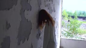 Η άγνωστη κόκκινη επικεφαλής γυναίκα με τη διανοητική ασθένεια κλίνει στον τοίχο του εγκαταλειμμένου σπιτιού απόθεμα βίντεο