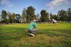 Η άγνωστη συμπύκνωση φορέων γκολφ και επιδιώκει τη σωστή γραμμή που κάθεται οκλαδόν σε πράσινο Στοκ Εικόνα