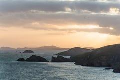 Η άγρια τραχιά ακτή του εθνικού πάρκου Pembrokeshire Με τα νησιά και τους απότομους βράχους που σκιαγραφούνται ενάντια στο ηλιοβα στοκ εικόνα με δικαίωμα ελεύθερης χρήσης