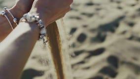 Η άμμος χύνει μέσω των χεριών των γυναικών στην παραλία φιλμ μικρού μήκους