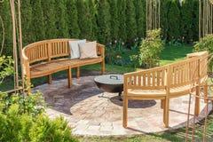 Η άνετη θέση στον κήπο που διαβάζει, χαλαρώνει και για τα άνετα βράδια από το κύπελλο πυρκαγιάς στοκ φωτογραφία με δικαίωμα ελεύθερης χρήσης