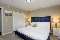 Η άνετη κρεβατοκάμαρα χαρακτηρίζει ένα μαύρο κρεβάτι και μπεζ τοίχους στοκ φωτογραφίες με δικαίωμα ελεύθερης χρήσης
