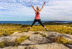 Η άνοιξη έχει αναπηδήσει το άλμα γυναικών μεταξύ των wildflowers Στοκ Φωτογραφίες