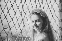 Η άνοιξη μόδας κοιτάζει Μικρό κορίτσι με το λουλούδι στην τρίχα σε καθαρό, την παιδική ηλικία και την ευτυχία Κομμωτής και hairst Στοκ Φωτογραφίες