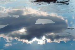 Η άνοιξη, σύννεφα αντανάκλασης ποτίζει, επιπλέοντα σώματα πάγου, ήλιος και σύννεφα που απεικονίζονται στους επιπλέοντες πάγους κα Στοκ εικόνα με δικαίωμα ελεύθερης χρήσης