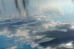 Η άνοιξη, σύννεφα αντανάκλασης ποτίζει, επιπλέοντα σώματα πάγου, ήλιος και σύννεφα που απεικονίζονται στους επιπλέοντες πάγους κα Στοκ φωτογραφία με δικαίωμα ελεύθερης χρήσης