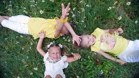 Η άποψη άνωθεν, παιδιά βρίσκεται στη χλόη, chamomile λιβάδι, και τεντώνει τα χέρια τους προς τα πάνω Έχουν τη διασκέδαση Καλοκαίρ απόθεμα βίντεο