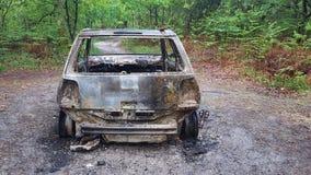 Η άποψη έκαψε έξω και σκουριασμένα συντρίμμια αυτοκινήτων παράλληλα με το δρόμο και τα ξύλα Στοκ φωτογραφίες με δικαίωμα ελεύθερης χρήσης