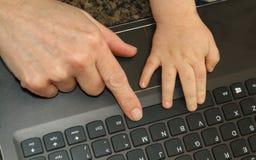 Η άποψη από την κορυφή του δάχτυλου μιας γυναίκας και childs δίνει σε ένα lap-top Κ στοκ εικόνες