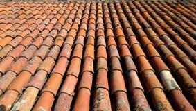 Η άποψη από την κορυφή των παλαιών κόκκινος-πορτοκαλής-καφετιών κεραμιδιών Η στέγη του παλαιού σπιτιού στοκ φωτογραφία με δικαίωμα ελεύθερης χρήσης