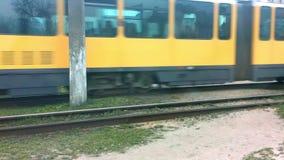 Η άποψη από το παράθυρο του αυτοκινήτου σε ένα περνώντας κίτρινο τραίνο τραμ απόθεμα βίντεο