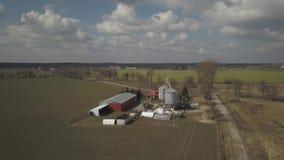 Η άποψη από το ύψος ενός μεγάλου αγροκτήματος που βρίσκεται μεταξύ των πράσινων λοφωδών τομέων Βίντεο από έναν κηφήνα ή ένα quadr φιλμ μικρού μήκους