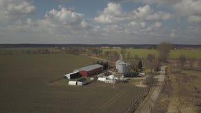 Η άποψη από το ύψος ενός μεγάλου αγροκτήματος που βρίσκεται μεταξύ των πράσινων λοφωδών τομέων Βίντεο από έναν κηφήνα ή ένα quadr απόθεμα βίντεο