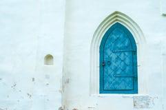 Η άποψη αρχιτεκτονικής των στοιχείων αρχιτεκτονικής γέρασε τη σκούρο μπλε σφυρηλατημένη μέταλλο πόρτα με το arcade στον άσπρο τοί Στοκ Εικόνες