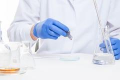 Η άποψη ενός ανθρώπου παραδίδει το εργαστήριο εκτελώντας τα πειράματα στοκ εικόνες