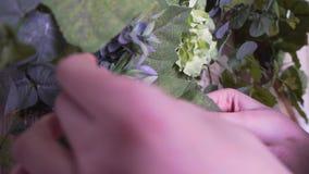 Η άποψη κινηματογραφήσεων σε πρώτο πλάνο, ένας ανθοκόμος γυναικών διακοσμεί ένα όμορφο ξύλινο photozone με τα λουλούδια φιλμ μικρού μήκους