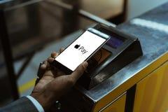 Η άποψη κινηματογραφήσεων σε πρώτο πλάνο του ατόμου που χρησιμοποιεί τη Apple πληρώνει την πληρωμή στοκ φωτογραφίες με δικαίωμα ελεύθερης χρήσης