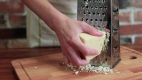 Η άποψη κινηματογραφήσεων σε πρώτο πλάνο του κοριτσιού στην κουζίνα τρίβει το τυρί στον ξύστη φιλμ μικρού μήκους