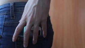 Η άποψη κινηματογραφήσεων σε πρώτο πλάνο του θηλυκού χεριού βγάζει ένα έξυπνο τηλέφωνο της οπίσθιας τσέπης τζιν απόθεμα βίντεο