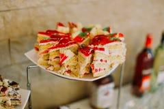 Η άποψη κινηματογραφήσεων σε πρώτο πλάνο των κέικ σφουγγαριών που διακοσμούνται με την κόκκινη ζελατίνα Στοκ Εικόνα