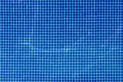 Η άποψη πέρα από την επιφάνεια νερού της πισίνας με τα μπλε κεραμίδια μωσαϊκών σχεδιάζει στο πάτωμα, νερό στην κίνηση Στοκ Εικόνες