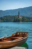 Η άποψη πέρα από τη λίμνη αιμορράγησε στη Σλοβενία με μια βάρκα κωπηλασίας στο πρώτο πλάνο στοκ φωτογραφίες με δικαίωμα ελεύθερης χρήσης