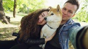 Η άποψη που πυροβολείται ομιλία του παντρεμένου ζευγαριού που παίρνει selfie με το σκυλί inu shiba κατοικίδιων ζώων, νέοι είναι,  απόθεμα βίντεο
