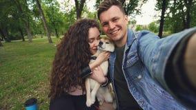 Η άποψη που πυροβολούνται δύο ευτυχών ανθρώπων και κουταβιού που παίρνουν selfie στο πάρκο, το φίλημα και η έκφραση αγάπης αγαπού απόθεμα βίντεο