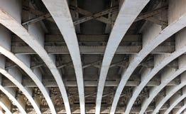Η άποψη προοπτικής των κυρτών τοξωτών δοκών χάλυβα κάτω από μια παλαιά οδική γέφυρα με τα καρφιά και τις δοκούς στέγης χρωμάτισε  στοκ φωτογραφία με δικαίωμα ελεύθερης χρήσης