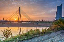 Η άποψη πρωινού σχετικά με το καλώδιο έμεινε γέφυρα και διαφορετικά κτήρια στη Ρήγα Στοκ Εικόνες