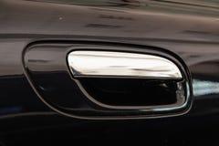 Η άποψη σχετικά με την κλειστή μαύρη μπροστινή πόρτα με τη λαβή έκανε από το χρώμιο του αυτοκινήτου πολυτέλειας μετά από να απαρι στοκ φωτογραφίες με δικαίωμα ελεύθερης χρήσης