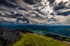 Η άποψη σχετικά με το Βόλφγκανγκ βλέπει από την κορυφή Schafberg μια ηλιόλουστη ημέρα με το δραματικό νεφελώδη μπλε ουρανό στοκ φωτογραφία