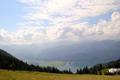 Η άποψη σχετικά με το πράσινο δάσος και ένα λιβάδι με μια λίμνη και τα βουνά στο υπόβαθρο Στοκ εικόνα με δικαίωμα ελεύθερης χρήσης