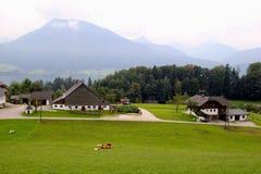 Η άποψη σχετικά με το πράσινο λιβάδι με τις αγελάδες, με τα σπίτια, μια λίμνη και τα βουνά στο υπόβαθρο Στοκ φωτογραφία με δικαίωμα ελεύθερης χρήσης