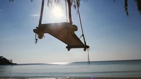 Η άποψη της παραλίας θάλασσας και η ξύλινη ταλάντευση κρεμούν κάτω από ένα δέντρο στην παραλία Διαφήμιση, ταξίδι, έννοια διακοπών απόθεμα βίντεο