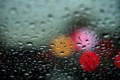 Η άποψη της πόλης νύχτας μέσω του παραθύρου σε μια βροχερή νύχτα, σταγόνες βροχής αφορά τον ανεμοφράκτη του αυτοκινήτου Ζωή έννοι Στοκ Εικόνες