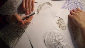 Η άποψη του πίνακα, τα σχέδια είναι στον πίνακα, το χέρι παίρνει τα σχέδια απόθεμα βίντεο