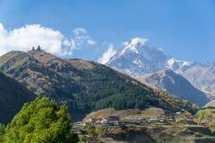 Η άποψη του χωριού Stepantsminda, εκκλησία τριάδας Gergeti και τοποθετεί Kazbek στον ηλιόλουστο καιρό Στοκ εικόνες με δικαίωμα ελεύθερης χρήσης