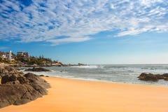 Η άποψη των αμμωδών ακτών στους όμορφους ουρανούς και το μικρό ho Στοκ Εικόνα