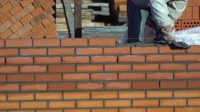 Η άποψη χρονικού σφάλματος του εργαζομένου χτίζει έναν τοίχο των τούβλων στη θερινή ημέρα ο οικοδόμος σε ένα κτήριο κάνει την πλι απόθεμα βίντεο