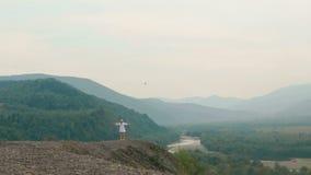 Η άποψη copter σχετικά με το γοητευτικό ξανθό τουρίστα που περιστρέφει γύρω από στο πλαίσιο των βουνών φιλμ μικρού μήκους