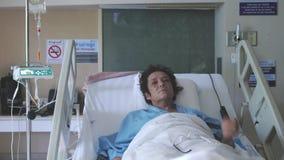 Η άρρωστη γυναίκα σε ηλικίας βρίσκεται σε ένα νοσοκομειακό κρεβάτι με μια μάσκα οξυγόνου κάτω από μια σταλαγματιά 1920x1080 απόθεμα βίντεο